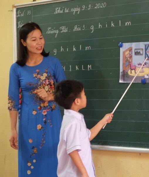 hình ảnh cô giáo và học sinh tập đọc
